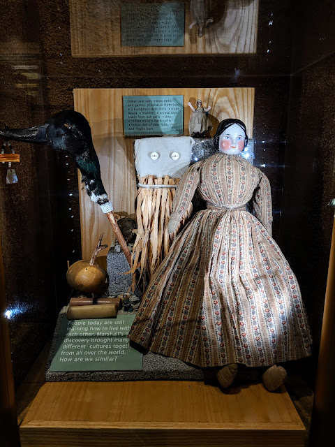 A Native American duck head on a stick and another of a stone with corn husk skirt bound around it are placed next to a porcelain doll with a painted face and cotton dress.