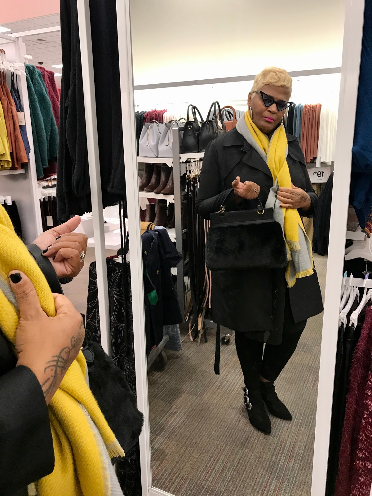 Woman trying on black purse and yellow scarf at Target. Outfit of the day