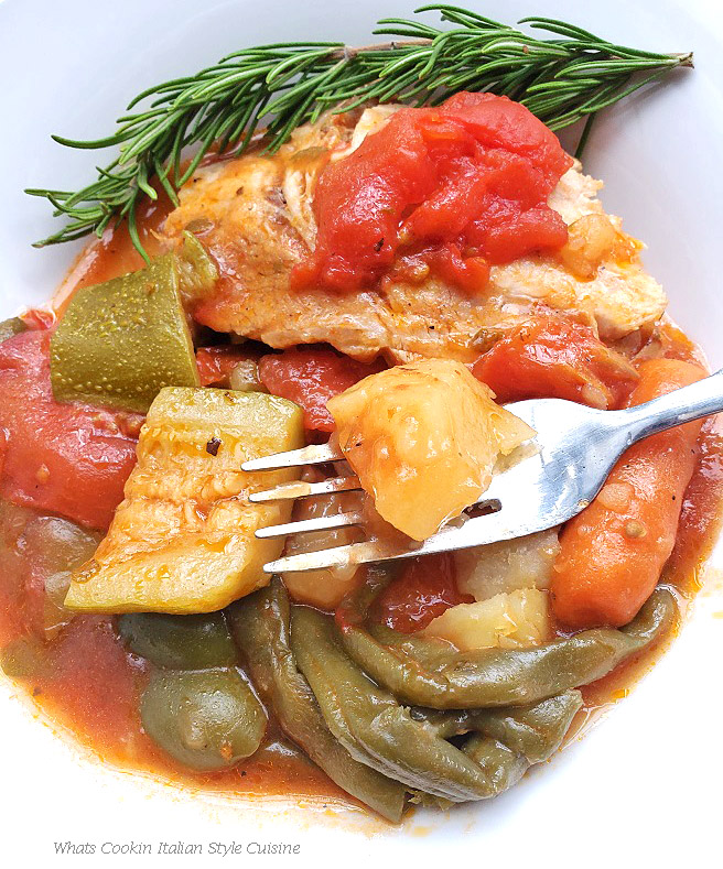 This is a big dish of stew with fresh garden vegetables in a rich beer sauce. The plate has pork roast sliced, potatoes, zucchini, green beans, carrots, fresh plum tomatoes with a fork in there ready to eat on a white plate.