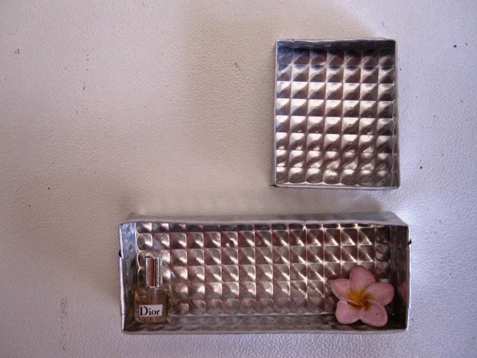 Two silver-coloured embossed metal dolls house wall boxes, one rectangular and one square, with a perfume bottle and frangipani in the lower one.