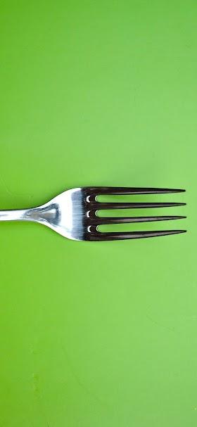 خلفية شوكة الطعام الفضية اللامعة أمام خلفية خضراء