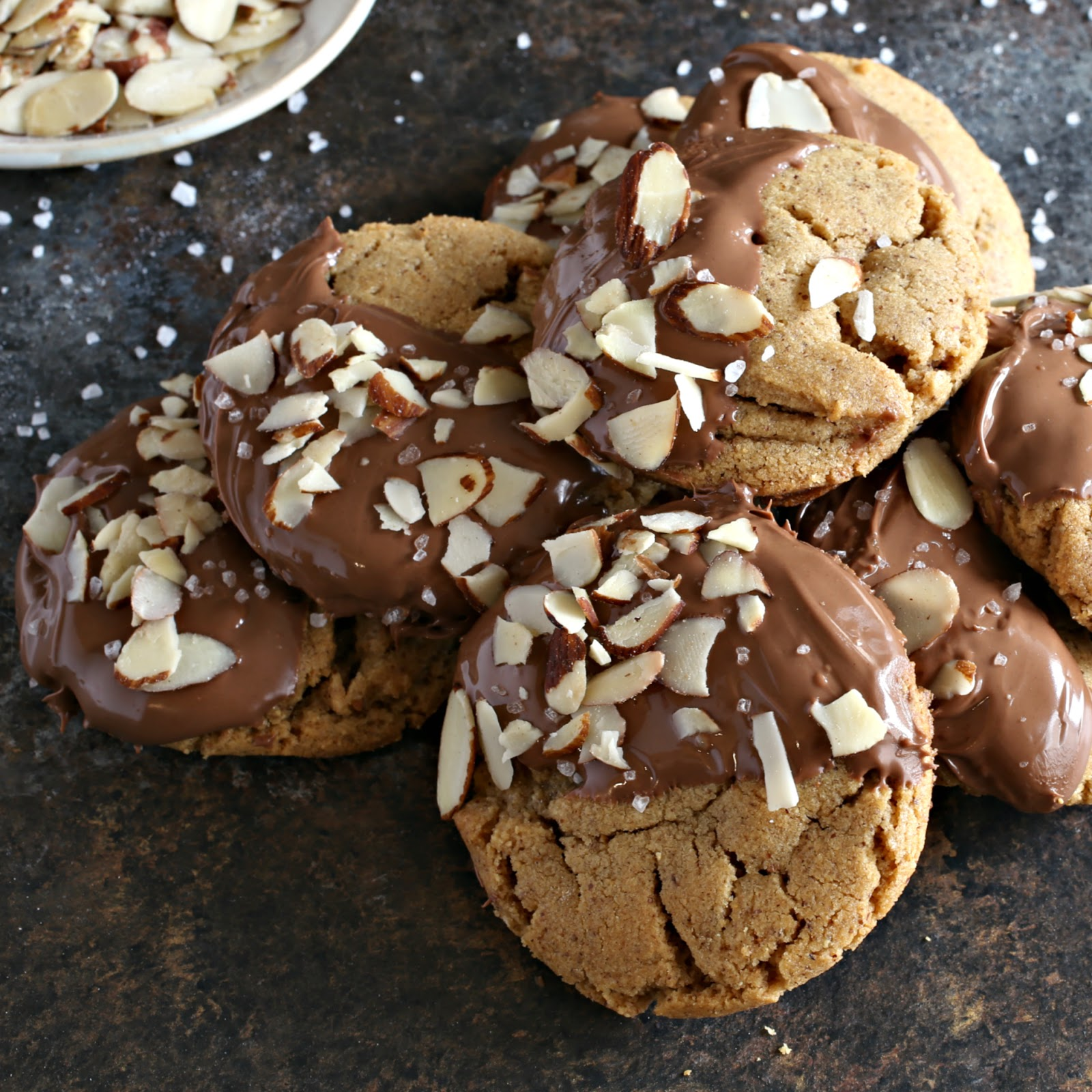 Almond butter cookies coated with chocolate and sprinkled with slivered almonds and sea salt.