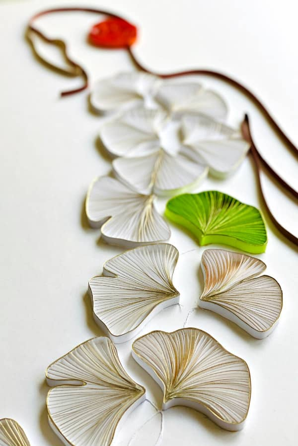 quilled on edge figure with ginkgo leaves