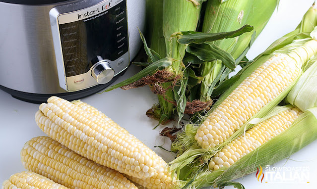 ingredients to make corn on the cob next to a pressure cooker