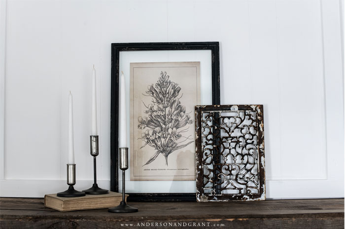 Collection of candlesticks, botanical print, and metal register cover.