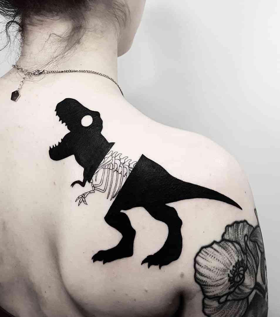 Vemos un tatuaje en blanco y negro de tiranosaurio