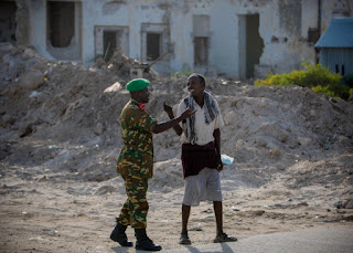 A Burundian officer serving with the African Union Mission in Somalia gestures with a Somali man August 6, 2012, in front of a war damaged building opposite the Aruba Hotel in the Somali capital Mogadishu