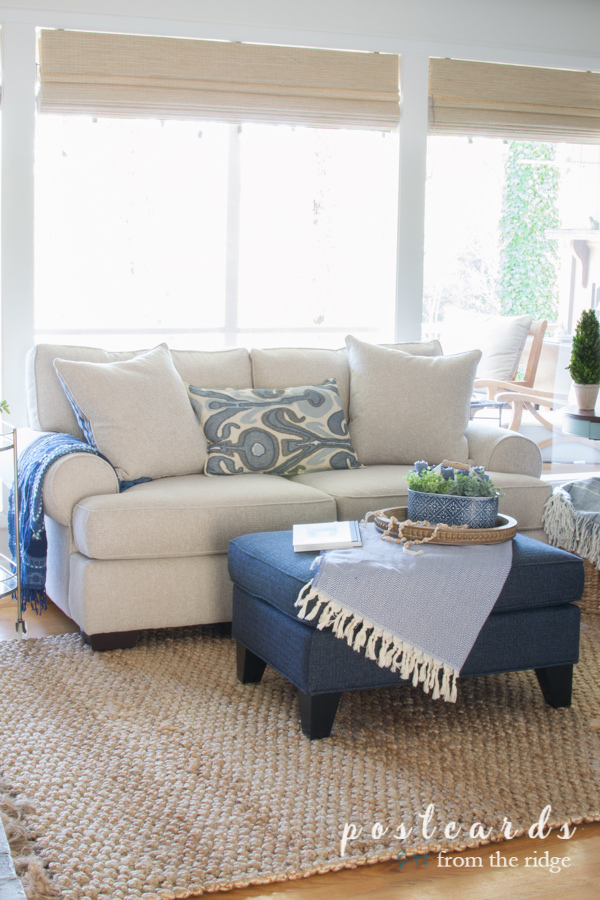 cozy living room with blue and white furniture and textured area rug