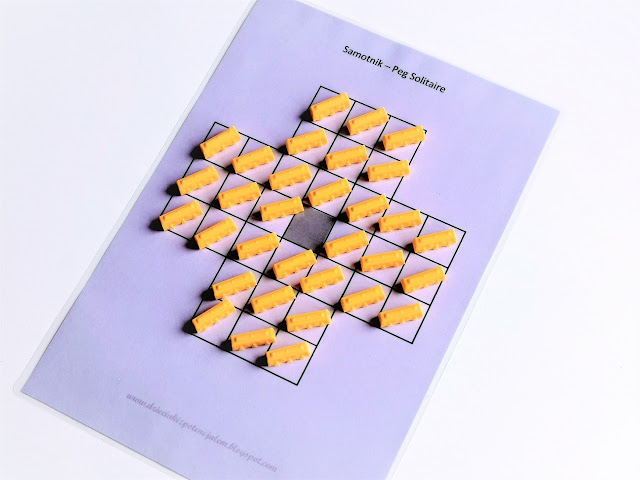 na zdjęciu wydrukowana i zalaminowana plansza do gry w samotnika, plansza ma kolor fioletowy i składa się z 33 kwadratowych pól ustawionych w kształt krzyża, na planszy leżą 32 pionki w kolorze pomarańczowym