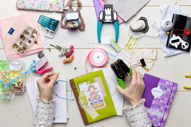 Flat lay showing different craft materials and equipment as someone sits scrapbooking