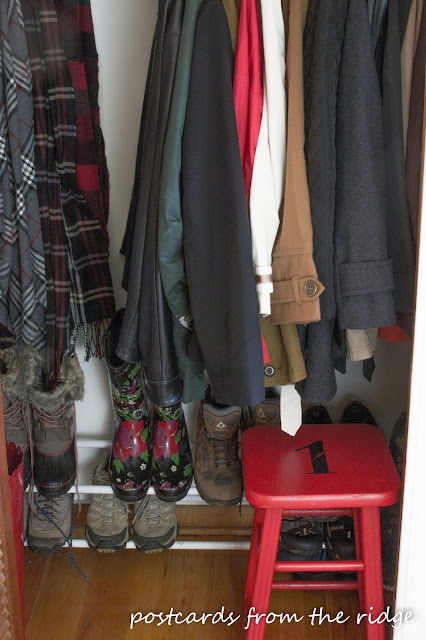 Red painted wooden stool in a coat closet. Great idea!