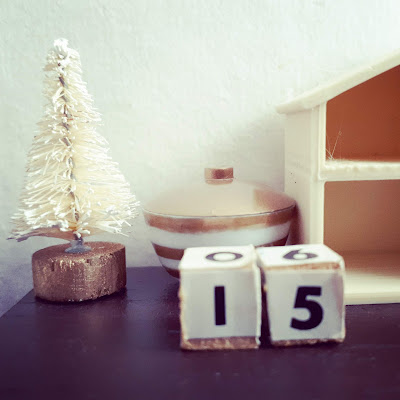 1/12 scale modern miniature tabletop scene in cream and brown containing a tiny bottlebrush Christmas tree, a lidded bowl with gold and white stripes, wooden blocks with the numbers '1' and '5' on them, and an empty dollshouse.