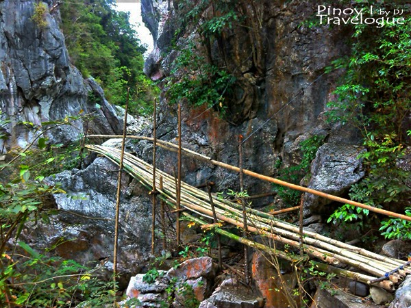Makeshift bamboo bridge leading to the limestone walls