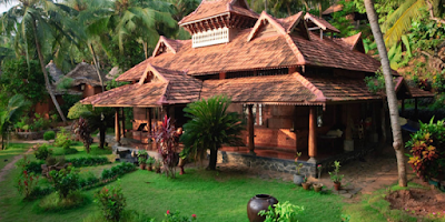 Beautiful view of Ayurvedic massage centre surrounded by tropical garden in Kerala, India, full of palms and different colorful flowers. Vacation and relaxing background.