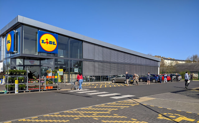 Photo of shoppers queuing 2m apart outside the Lidl store in Maryport, Cumbria, UK