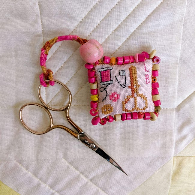 cross stitched scissor fob with wooden beads around the edges attached to pair of scissors, the cross stitch is of scissors a spool buttons and a safety pin along with initials LB