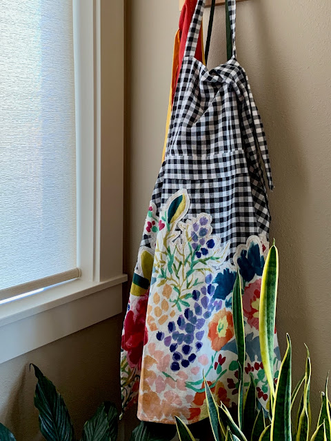 Modern apron on wall hook, black and white  check, colorful flower applique,