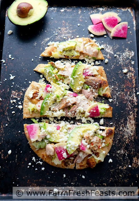 A fast and easy fresh tasting pizza this simple naan crust is topped with mahi mahi, sautéed Napa cabbage, avocados, watermelon radishes, and crumbled queso.