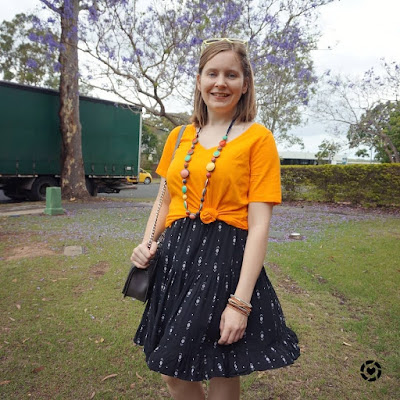 awayfromtheblue Instagram | marigold orange tee with black sundresses knotted spring layer bright necklace love bag