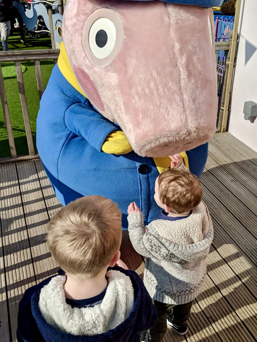 two children meeting life size george pig character at peppa pig world paultons park