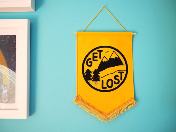 a yellow pennant sign with tassel trim. On it there is a black circle with trees, hills, and the words 'get lost' in it.