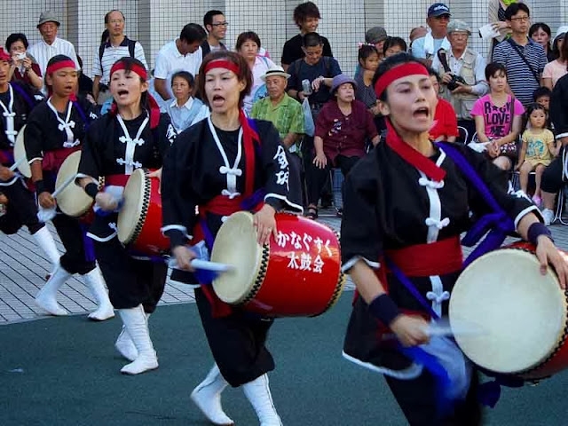 youngsters in costume dance Eisa and beat drums, while chanting