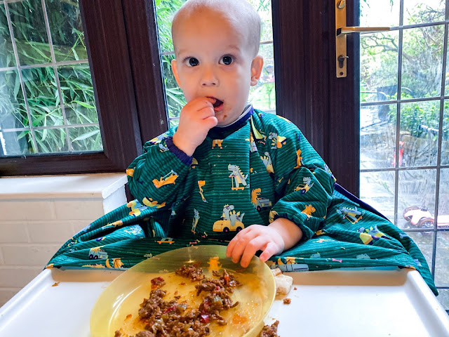 Baby eating food in a green dinosaur coverall all BIBaDO bib