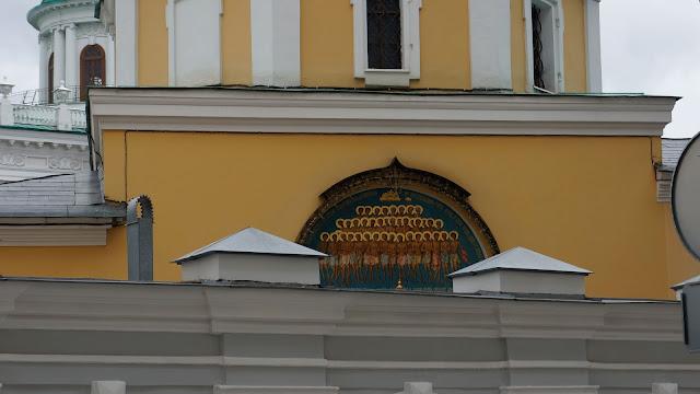 На фото видно изображение настенной росписи за забором храма