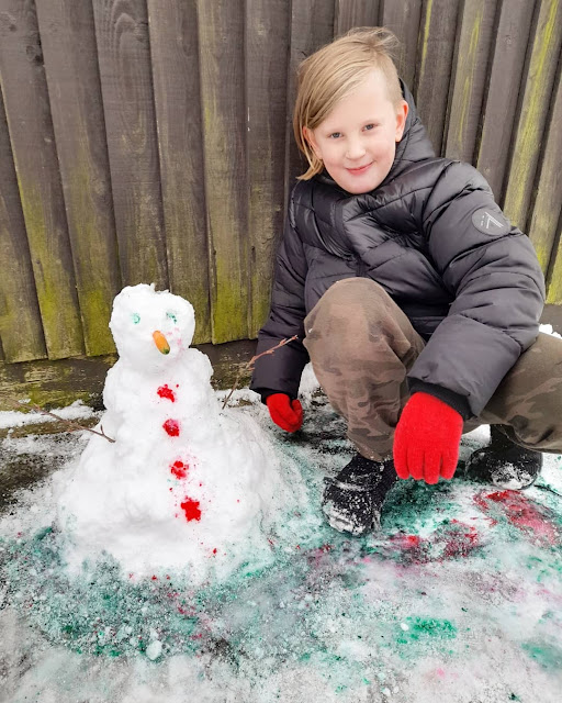 A crouches next to the snowman. He is also wearing red gloves and smiling
