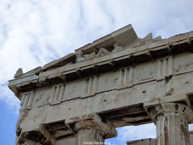 fragment Partenonu na którego zadaszeniu znajduje się posąg Apollona Partenon, na niebie gęste białe chmury, Ateny Grecja