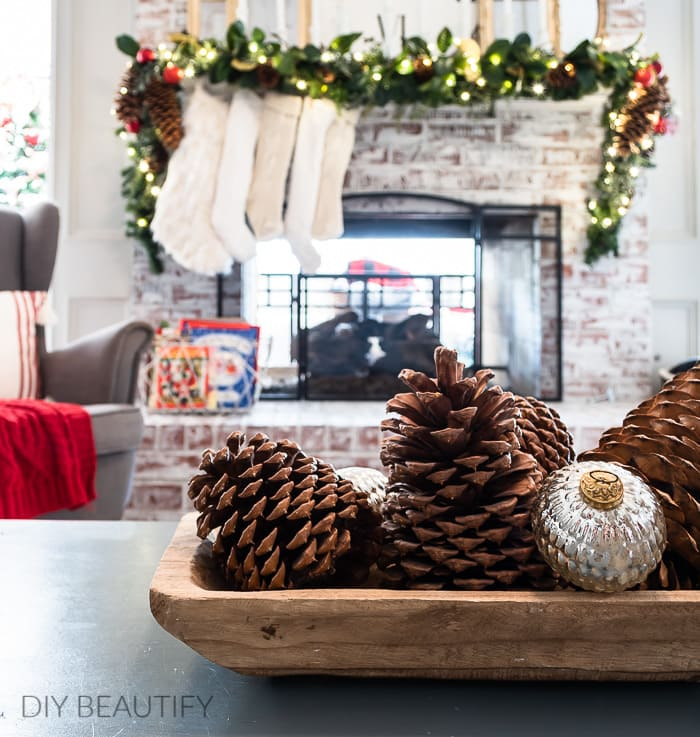 pinecones and ornaments in wood bowl