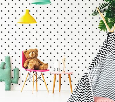 Decoración infantil moderna compuesta por una pared empapelada con topos negros.
