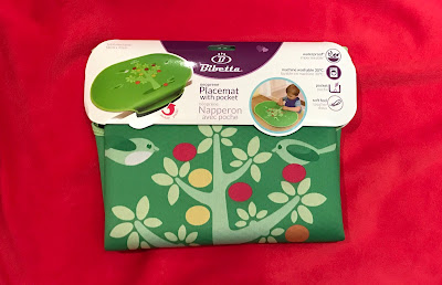 The Bibetta placemat with pocket in it's packaging on a red background
