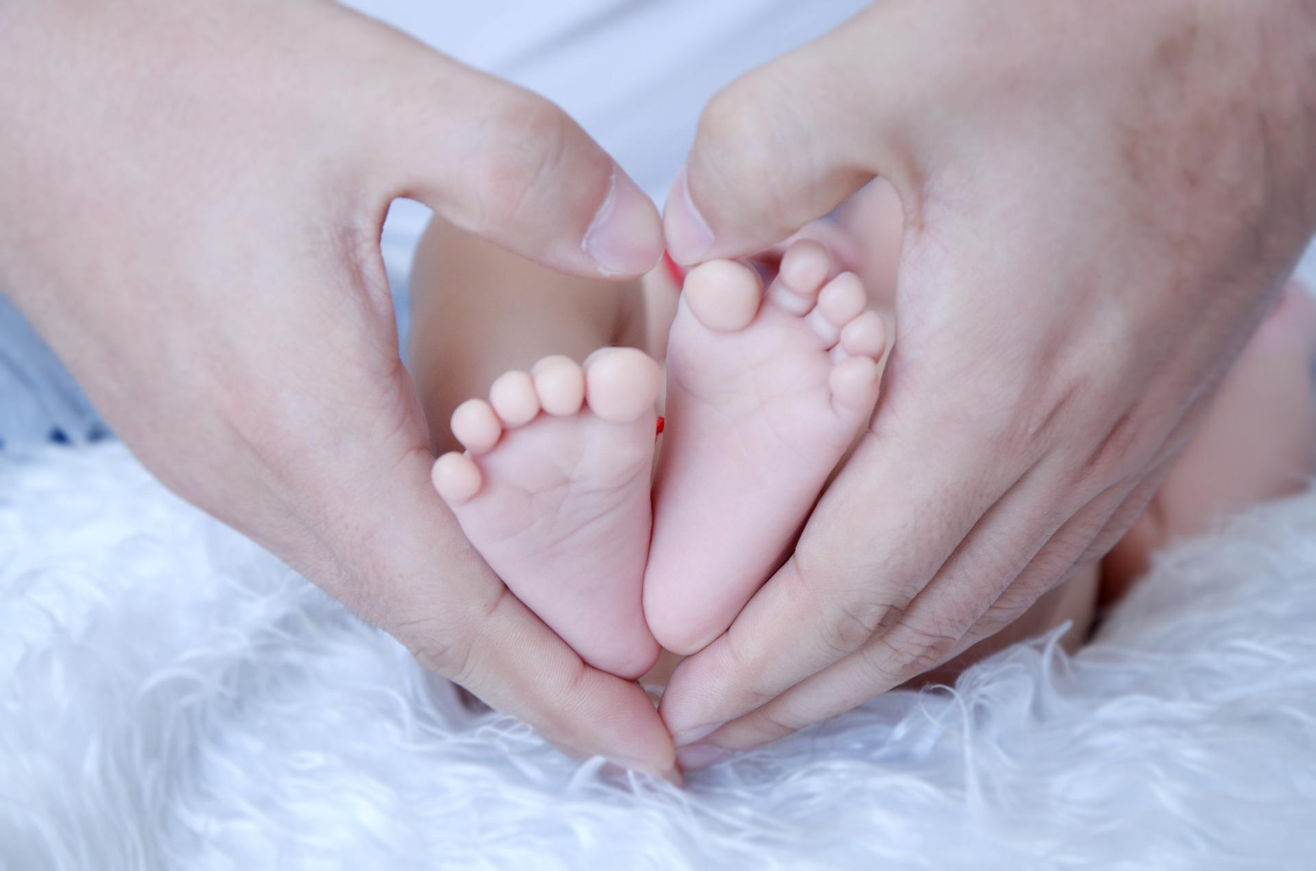 صورة جميلة لأب وابنه متضمنة أقدام الطفل ويدي الأب على شكل قلب