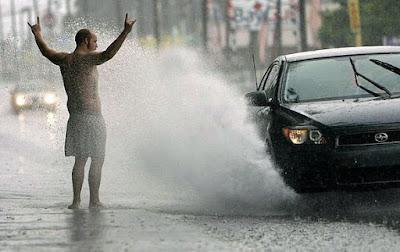 Vom Auto nass gespritze - lustige Menschen im Regen