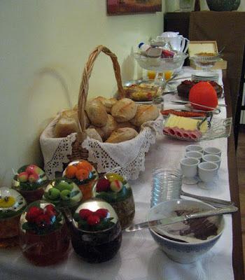 mesa posta com cesto de pães, vidros de compostas e queijos