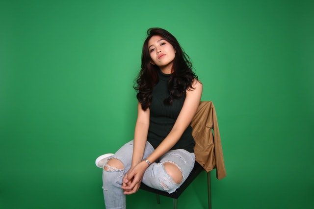 foto model cantik duduk di kursi green screen background