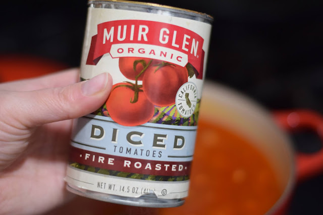 A can of fire roasted diced tomatoes being added to the pot.