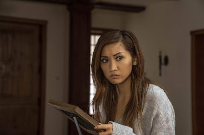 "Movie still for the Netflix original ""Secret Obsession"" where Brenda Song inspects a photoshopped picture of her husband while he is out of the house"