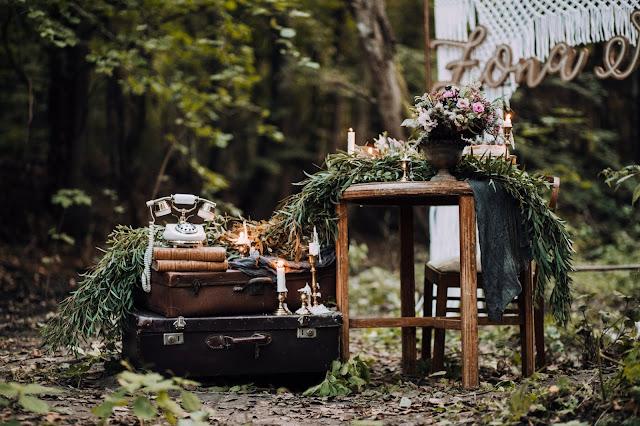 Dekoracji z nutką vintage: zabytkowy telefon, stare walizki, pamiątkowe książki, zielona girlanda, złote świeczniki.