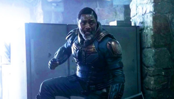 Imagem: o personagem Bloodsport, interpretado por Idris Elba, um homem negro em um traje tecnológico de couro com placas metálicas em posição de luta em algum tipo de galpão.