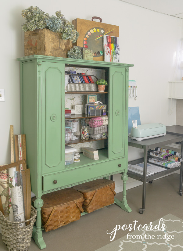 vintage china cabinet repurposed as storage cabinet for art and craft supplies