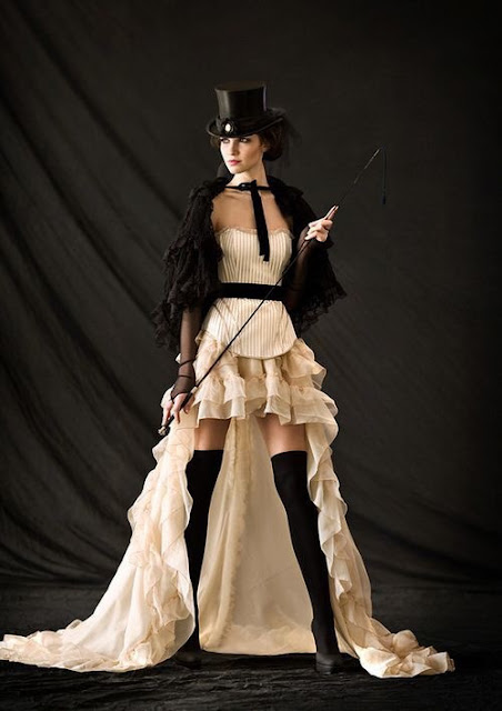 A woman wearing victorian clothing--a top hat, corset, showgirl skirt, shawl and stockings. Women's steampunk clothing with a neo-victorian emphasis.
