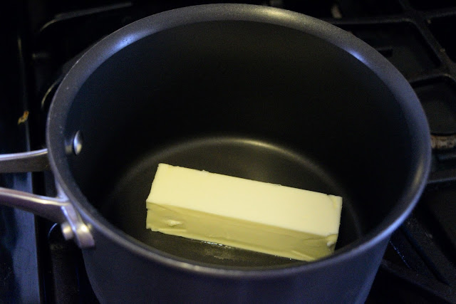 A stick of butter in a sauce pan.