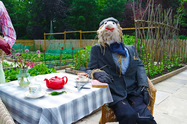 male scarecrow sat at a table with a red teapot and floral teacups