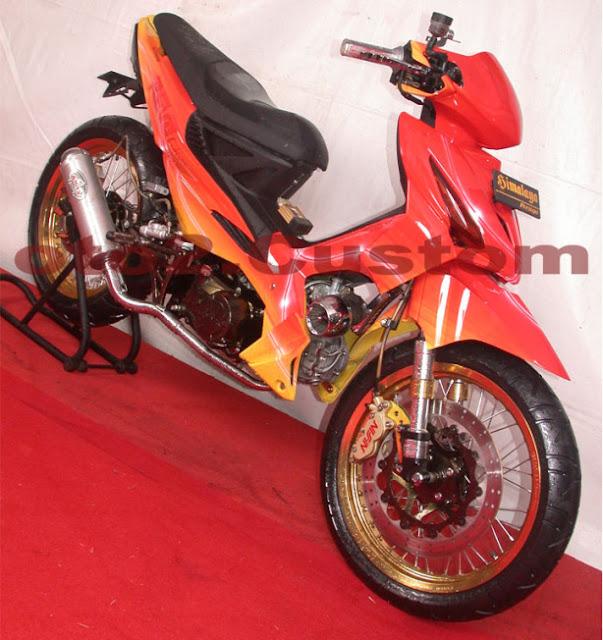 Foto Modifikasi Honda Revo dengan modif Racing Road Race didominasi warna yang mencolok yakni oranye dan sedikit warna kuning dibagian bawah bodi motor untuk belakang jok dibuat meruncing tak lupa jari-jari dibuat rapat lurus untuk pada bagian velg diwarna oranye