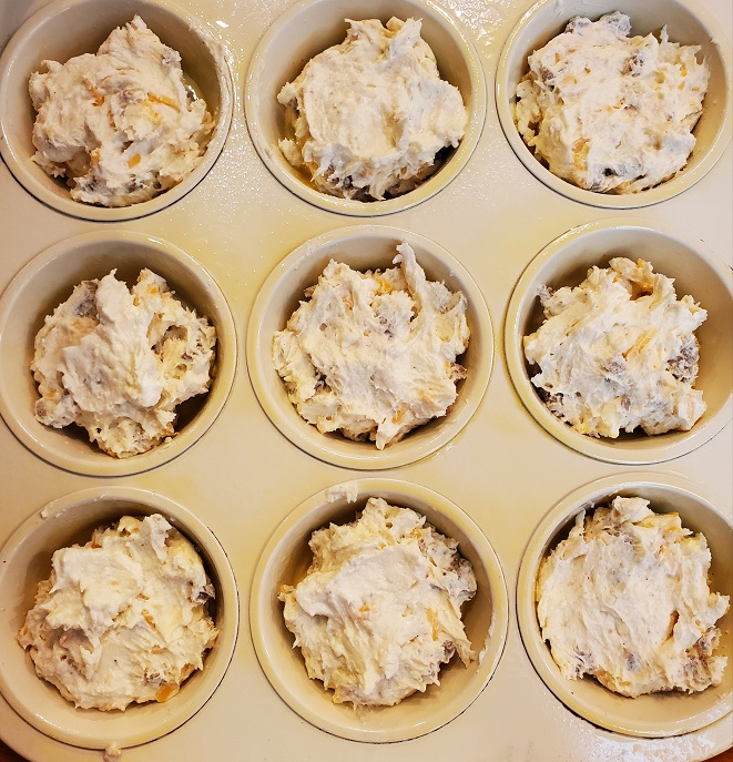 this is a muffin tin filled with sausage and cheese batter for biscuits