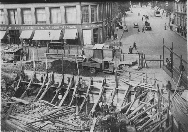 """Начало 1930-х годов. Рига. Угол улиц Калькю и Вальню. Строится здание по адресу ул. Вальню, 11 (будет построено в 1931-м году). На часах реклама """"Th. Riegert"""". Постамент без памятника Петру I"""