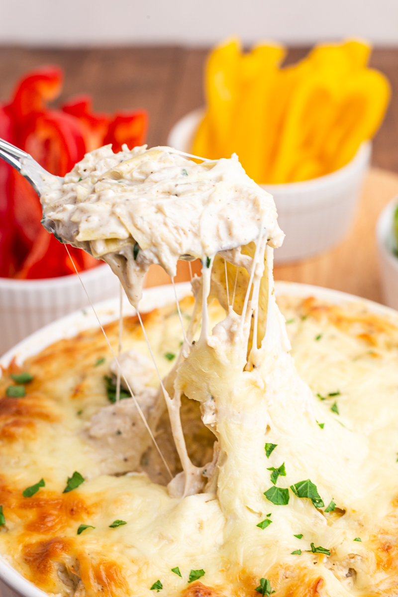 Photo of Low Carb Artichoke Crab Dip in a white bowl with a spoon scooping out a serving.