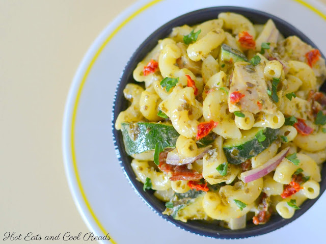 Chicken Pesto Pasta Salad Recipe from Hot Eats and Cool Reads! This elbow macaroni pasta salad is packed with chicken, bacon, sun dried tomatoes, zucchini and so much more! Great for any summer picnic or barbecue!